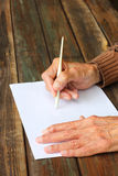 Close up of elderly male hands on wooden table . writing on blank paper. Close up of elderly male hands writing on blank paper Stock Photography
