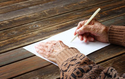 Close up of elderly male hands on wooden table . writing on blank paper. Close up of elderly male hands writing on blank paper Royalty Free Stock Image
