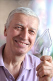Elderly man doing inhalation Stock Images