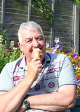 Close up of elderly man eating an ice cream. Royalty Free Stock Image
