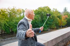 Close-up of an elderly man in a gray jacket and white shirt with a monopod in his hands, shoots a video. Royalty Free Stock Photography
