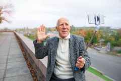 Close-up of an elderly man in a gray jacket with a monopod in his hands, shoots a video Royalty Free Stock Photos