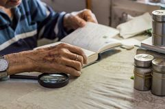 Close up of an elderly man hand holding a notebook near the window in the kitchen Royalty Free Stock Images