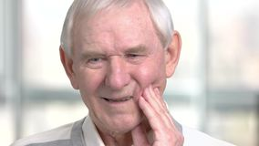 Close up elderly man having toothache. Old man touching his cheek and suffering from tooth ache, blurred background. Dentistry problem concept stock footage