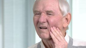 Close up elderly man with toothache. Senior man suffering from terrible toothache close up, blurred background. Dentistry and health care stock video footage