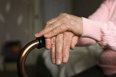 Close up of elderly woman holding a walking cane in nursing home. royalty free stock images