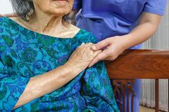 Elderly woman holding hand with caregiver royalty free stock photo