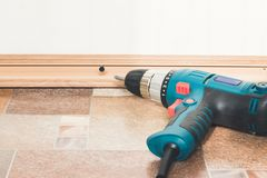 Installation of plastic floor plinth. Interior details. Close up electric drill and nails left on wooden floor. Installation of plastic floor plinth royalty free stock photography