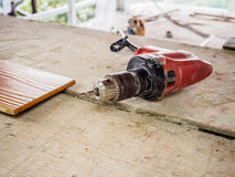 Close up electric drill at work site. On wooden board Stock Images