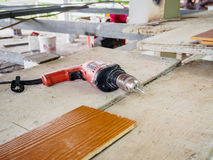 Close up electric drill at work site. On wooden board Stock Photography