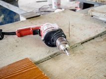 Electric drill at work site on wooden board. Close up electric drill at work site on wooden board Stock Photo