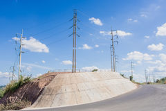 Electric pole on a hill next to the road at a curve. Stock Photography