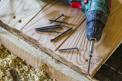 Close up of electric screwdriver with some screws laying on old. Rough wooden table or vintage natural planks. Building, repairing and home maintenance concept Royalty Free Stock Images