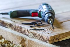 Close up of electric screwdriver with some screws laying on old. Rough wooden table or vintage natural planks. Building, repairing and home maintenance concept Royalty Free Stock Photo