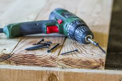 Close up of electric screwdriver with some screws laying on old. Rough wooden table or vintage natural planks. Building, repairing and home maintenance concept Stock Images