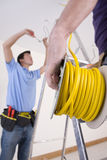 Close up of electrician holding cable spool with co-worker wiring ceiling in background Stock Image