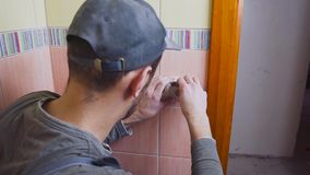 Close-up of an electrician with a screwdriver seting up a white outlet, the concept of electrification of the room is. The construction or repair stock video