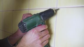 Close-up of an electrician with a screwdriver seting up a white outlet, the concept of electrification of the room is. The construction or repair stock video footage