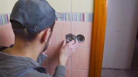 Close-up of an electrician with a screwdriver seting up a white outlet, the concept of electrification of the room is. The construction or repair stock footage