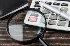 Close up of electronic calculator, notepad, magnifying glass and Stock Photography