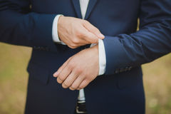 Close-up of elegance male hands wearing modern suit Stock Photo