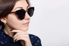 A close-up of elegant brunette woman with pure skin wearing sunglasses isolated over white background having serious expression th Royalty Free Stock Photos
