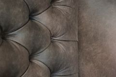 Close-up of elegant Chesterfield chair. Brown leather chair. Seat and back with buttons. With free space for text. royalty free stock photo