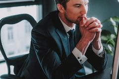 Close up of elegant man putting chin on the hands while thinking royalty free stock image