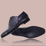 Close-up of elegant mens shoes on beige background royalty free stock image