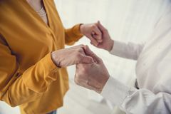 Loving mature couple bound in matrimony. Close up of elegant old woman holding hands with aging gentleman. Top view Stock Photos