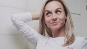 CLose up of Elegant young woman looking at mirror and touching her face in bathroom