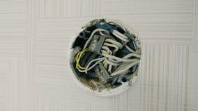 Close-up elektrokabeldoos op de muur onder het plafond stock video