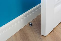 Close-up elements of the interior of the apartment. Metal chrome door stopper on laminate floor.  stock image