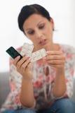 Close up em comprimidos à disposição de jovem mulher interessada fotografia de stock royalty free