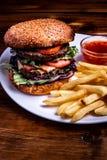 Close-up em hamburgueres de uma carne da placa de madeira, naco friável, alface, queijo, pepinos, alimento na moda, restaurante fotos de stock royalty free