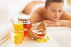 Close up em ingredientes e em mulher da terapia dos termas do mel no fundo imagens de stock