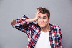 Close up of embarrassed man scratching head and looking confused Royalty Free Stock Photo
