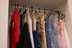 Close-up embroidered with stones and sequins top pink wedding dress which hangs on a hanger among other dresses. glamour royalty free stock photography