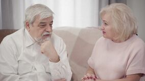 Close-up of emotional mature Caucasian woman scolding elderly husband at home. Displeased couple of retirees arguing