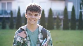 Portrait of teen boy with backpack. Close up emotional portrait of caucasian smiling teen boy with backpack. Happy cute student teenager against the background stock video footage