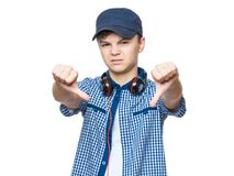 Teen boy with cap and headphones. Close up emotional portrait of caucasian unhappy teen boy giving thumbs down hand gesture. Angry child looking with disapproval Stock Images