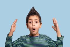 Close up  portrait of  a funny boy  surprising or delighting with something, raising his hands up on blue background in studio. Close up  emotional portrait of royalty free stock images