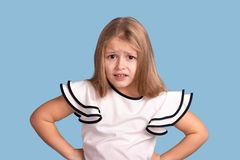 Close up emotional portrait of young blonde  girl  on blue background in studio. She  holds her hands at the waist and is. Complaining about something  or royalty free stock images