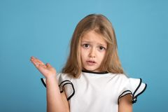 Close up emotional portrait of young blonde girl wearing white blous with black strips on blue background in studio. She shows royalty free stock image