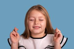 Close up emotional portrait of young blonde  smiling girl  on blue background in studio. She crossed her fingers, closed her eyes royalty free stock images
