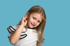Close up emotional portrait of young blonde smiling girl on blue background in studio. She. Close up emotional portrait of young blonde smiling girl wearing royalty free stock photography
