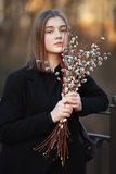 Close up emotional portrait of young happy beautiful woman with a bouquet of pussy-willows wearing black coat posing on park bridg Stock Photography