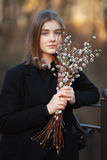 Close up emotional portrait of young happy beautiful woman with a bouquet of pussy-willows wearing black coat posing on park bridg Stock Photos