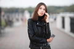 Close up emotional portrait of a young pretty brunette woman posing full length outdoors city park wearing black leather coat hold Stock Photography