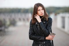 Close up emotional portrait of a young pretty brunette woman posing full length outdoors city park wearing black leather coat hold. Emotional portrait of a young Stock Image